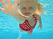 picture of young baby  - Happy young girl swimming underwater in pool