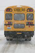 stock photo of driving school  - School bus driving in snowy winter scene on icy road - JPG
