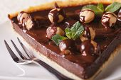 picture of tarts  - A piece of chocolate tart with hazelnuts on a white plate close - JPG