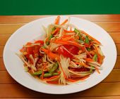 image of green papaya salad  - thai hot papaya salad with a green background on a wood table top - JPG