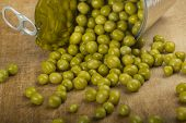 foto of green pea  - Green peas spilling out of a tin can over wood background - JPG