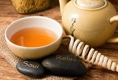 picture of ceremonial clothing  - Horizontal photo of relaxing scene with oriental tea in cup near tea pot with two lava stones placed on jute cloth - JPG
