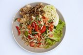 stock photo of green papaya salad  - papaya spicy salad with salmon on white table in restaurant - JPG