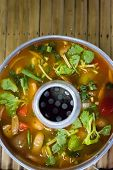 stock photo of gai  - Tom yum soup in traditional dishware in a street restaurant - JPG