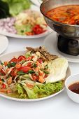 picture of green papaya salad  - papaya spicy salad with salmon on white table in restaurant - JPG