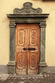 picture of wall-stone  - Vintage brown wood medieval door with ornate stone portal in rural stone wall house - JPG