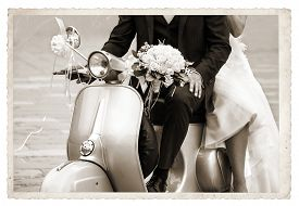 stock photo of grayscale  - Vintage photo with Young newlywed just married posing on an old gray scooter - JPG