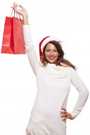 pic of vivacious  - Happy vivacious Christmas shopper wearing a red Santa hat holding up a colorful red shopping bag with a beautiful beaming smile isolated on white with copyspace - JPG
