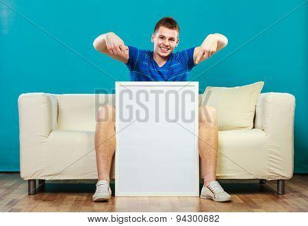 Man On Sofa Holding Blank Presentation Board