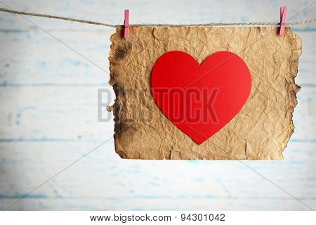 Bright heart and card hanging on rope on wooden background