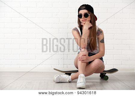 Beautiful hipster girl with skateboard on light background
