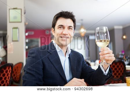 Man drinking a glass of white wine in a restaurant
