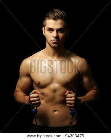 Muscle young man exercising with resistance band on dark background