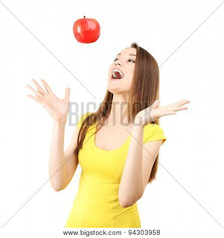 Healthy young woman throwing up red apple isolated on white