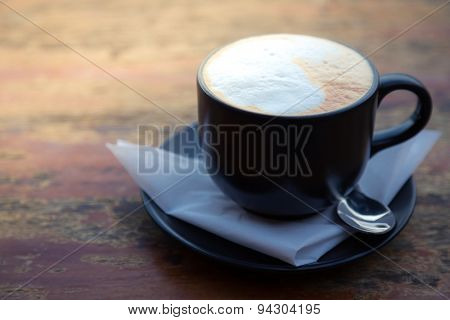 Coffee in black cup on wood table