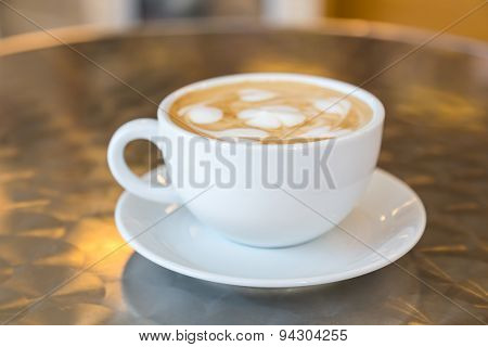 Cup of coffee with heart pattern in a white cup on