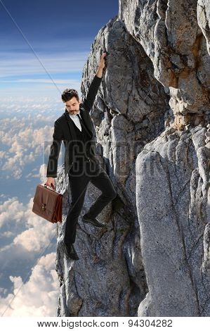 Young businessman clinging onto rock with clouds in background