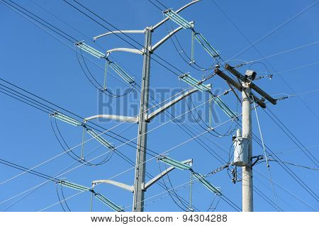 Old and new electrical line towers during sunny day