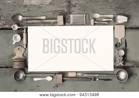 Old white kitchen message sign with cooking utensils for a frame on ancient wood.