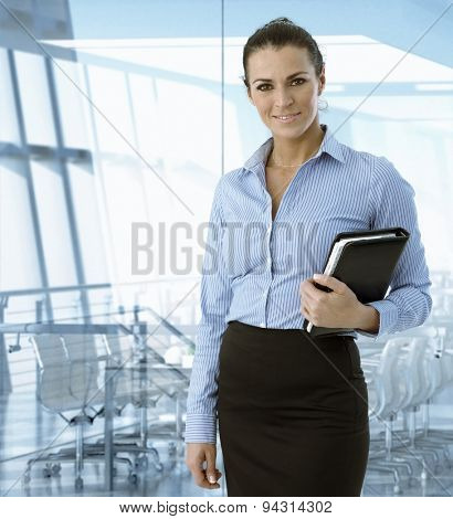 Executive caucasian businesswoman standing in front of meeting room, smiling.