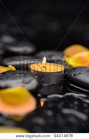 Still life with yellow rose petals with candle and therapy stones