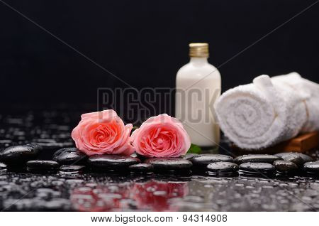 Two rose and towel with massage oil and therapy stones
