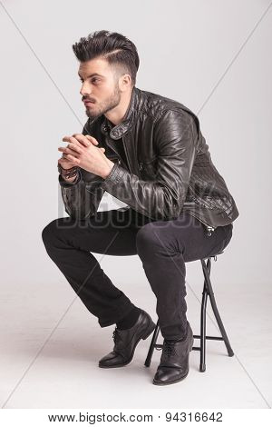 Side view picture of a fashion man holding his hands together while resting on a chair.