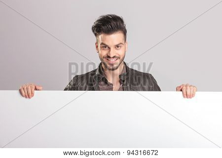 Happy young fashion man smiling to the camera while holding a white board.
