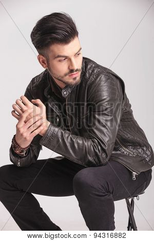 Attractive young fashion man sitting on a chair while looking to his side.