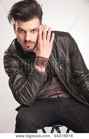 Potrait of a young attractive fashion man sitting while holding his hand near his face.