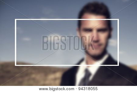 Businessman standing outdoors staring directly at the camera.