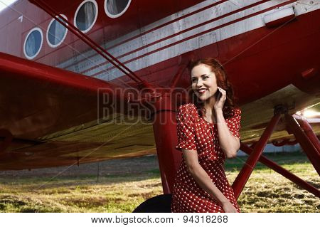 laughing pin-up female sitting on plane wheel in dress