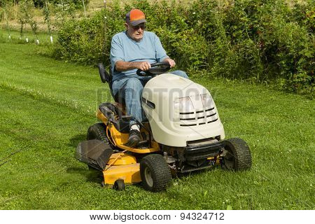 Older Gentleman Cutting Gas On Riding Lawnmower