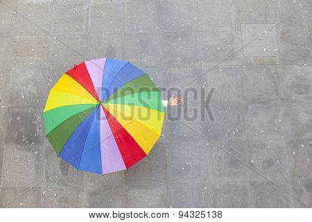 Woman hidden under multicolor umbrella