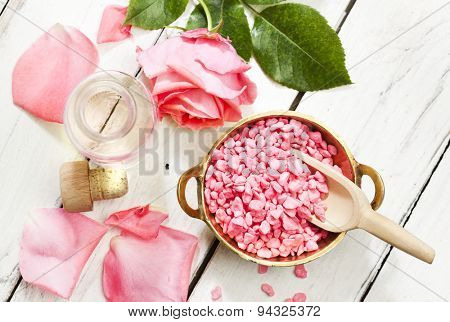 Essential oil and bath salt with rose and petals on wooden background