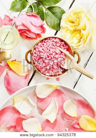 pink and yellow roses, petals, bath salt aromatic essence, top view, wood background