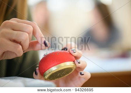 Woman holding a pin cushion
