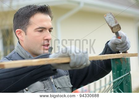 Hammering a fence into place