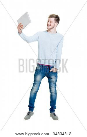 Teenage student holding a tablet computer and making a selfie isolated on white