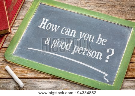 How can you be a good person? An inspirational question on a  blackboard with a white chalk and books against rustic wooden table