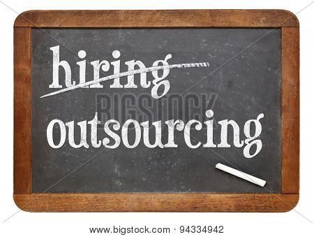 outsourcing instead of hiring concept - white chalk text on a vintage slate blackboard