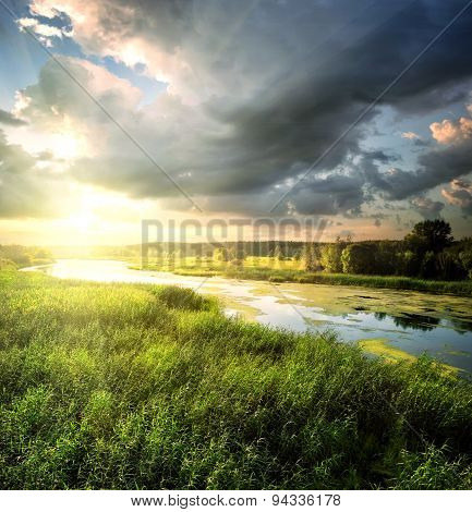 River flows through the field with lush green grass