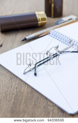 Spiral notebook with vintage cover with pen, pencil, eraser and glasses, selective focus