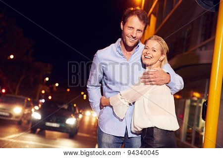 Couple embracing on city street at night, portrait