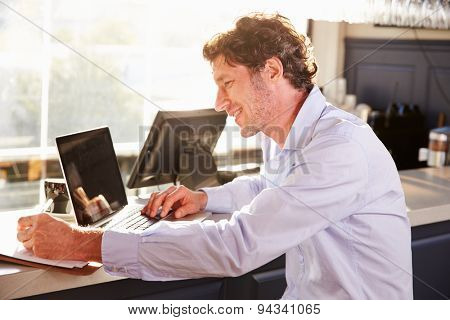 Male restaurant manager working on laptop