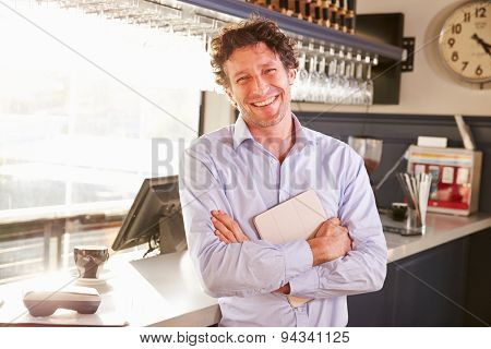 Male restaurant owner holding digital tablet, portrait