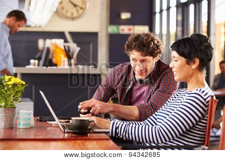 Man and woman using laptop at a coffee shop