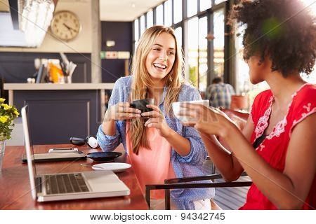 Two women with computer laughing in a coffee shop