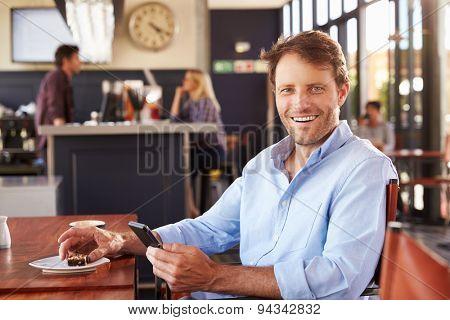 Man using smart phone in a coffee shop, portrait