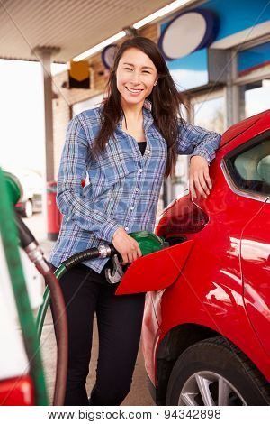 Woman refuelling a car at a petrol station
